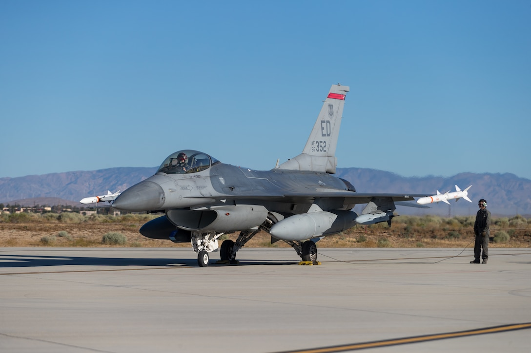 F-16 Fighting Falcon crew chief, Airman 1st Class Wyatt Hegner, prepares Maj. Jacob Schonig, 416th Flight Test Squadron, for a captive-carry flight test of the Gray Wolf cruise missile prototype at Edwards Air Force Base, California, June 9. (Air Force photo by Kyle Brazier)