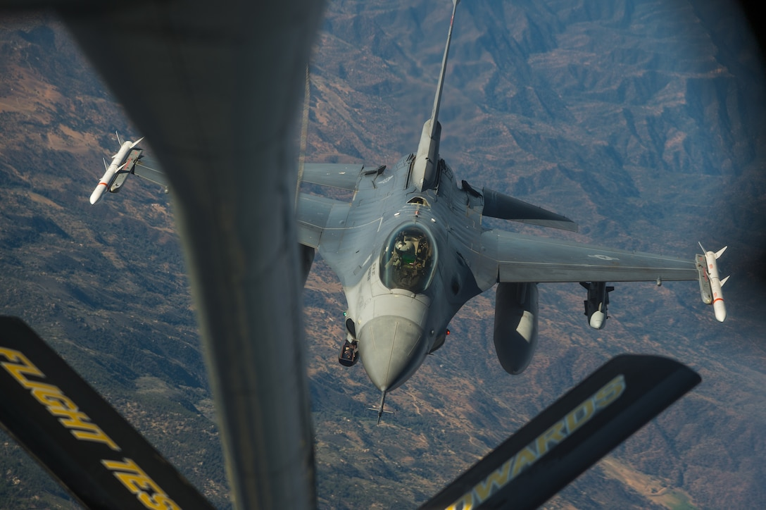 An F-16 Fighting Falcon flown by Maj. Jacob Schonig from the 416th Flight Test Squadron at Edwards Air Force Base, California, conducts a mid-air refueling operation with a KC-135 Stratotanker during a captive-carry flight test of a Gray Wolf cruise missile prototype, June 9. (Air Force photo by Ethan Wagner)