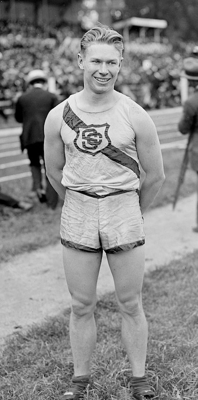A young man wearing shorts and a T-shirt emblazoned with a team logo poses for a photo standing outside on an athletic field.