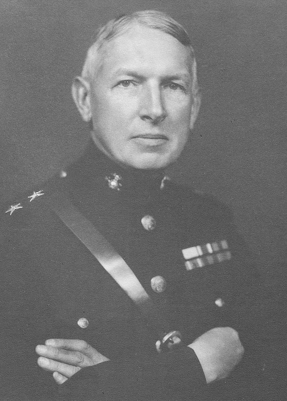 A young man wearing a dress uniform poses for a photo with his arms crossed on his chest.