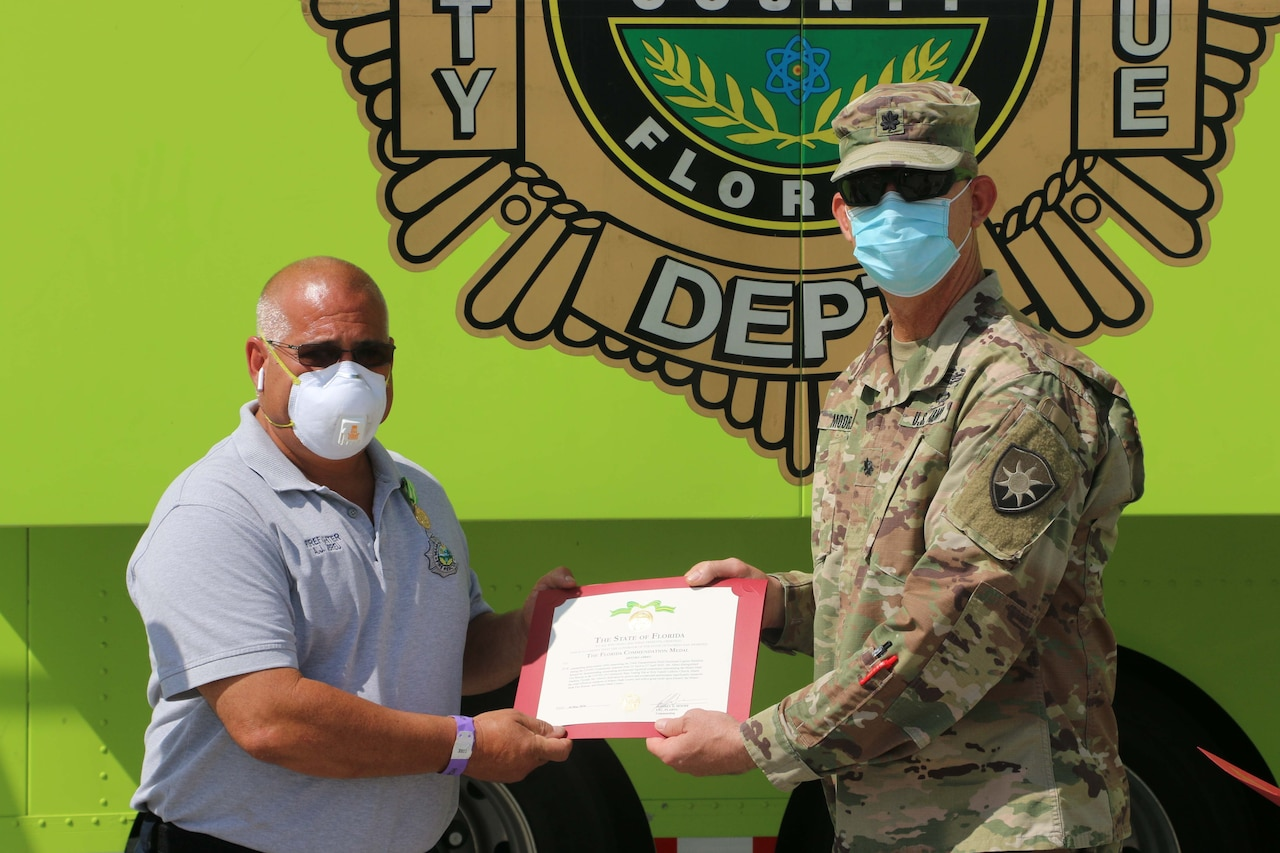 A soldier presents an award to a civilian.