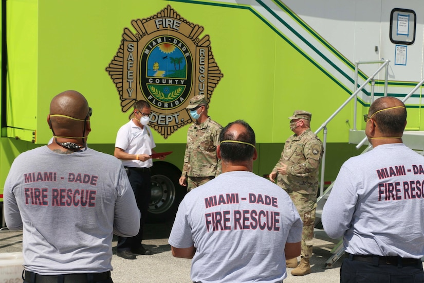 Two soldiers congratulate a civilian as men wearing Miami-Dade County Fire Rescue T-shirts look on.