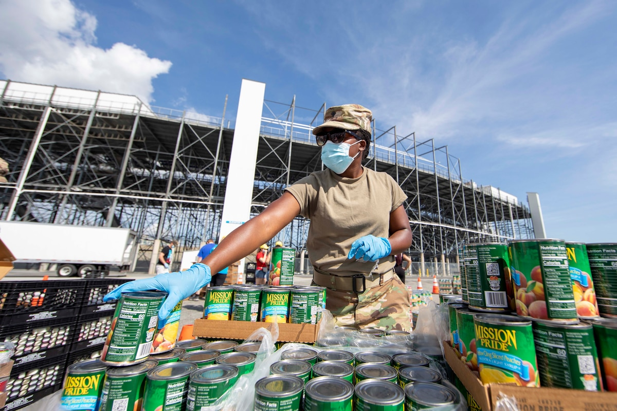 A soldier arranges cans of food on a table.