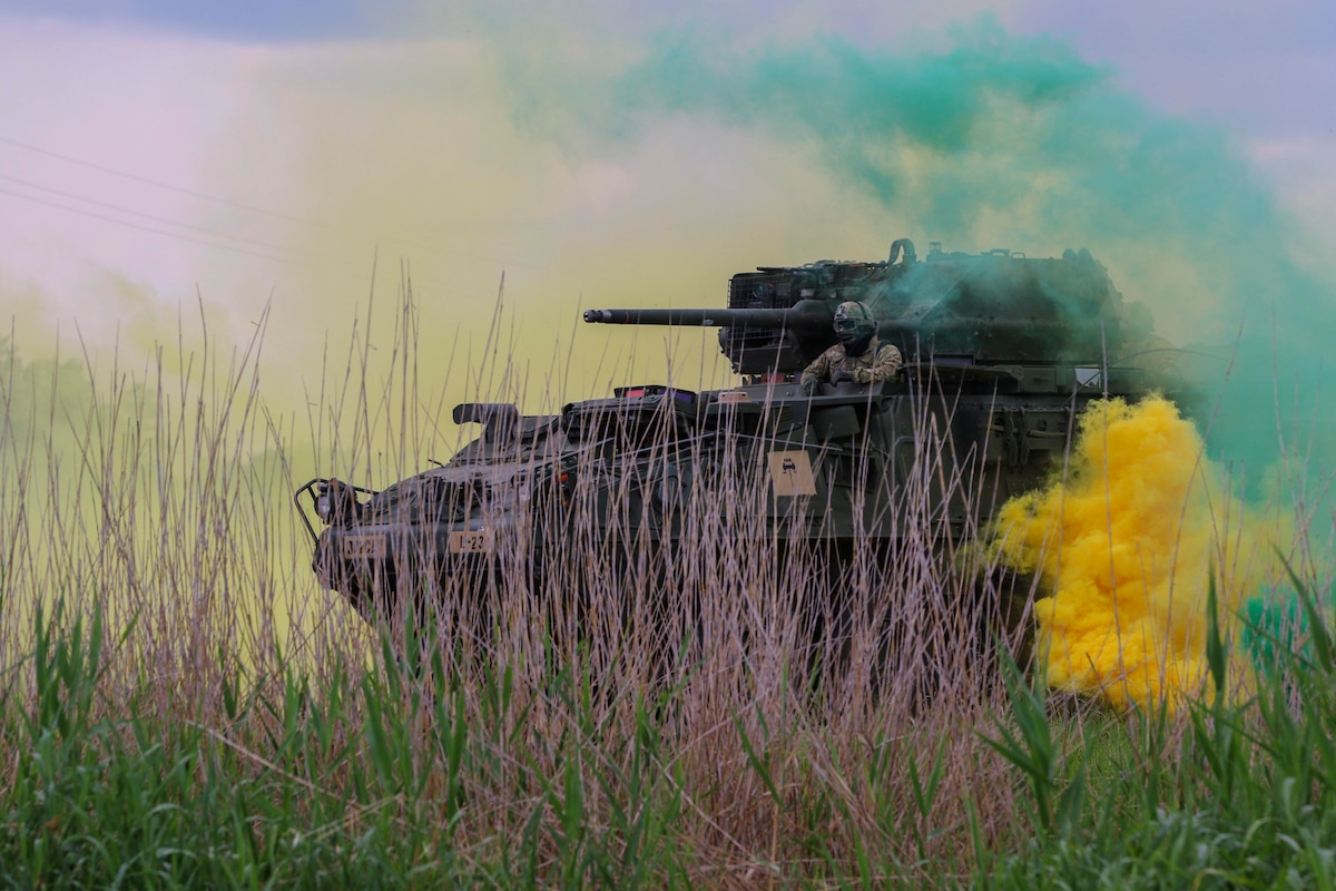 Soldiers in a tank ride through yellow and green smoke.
