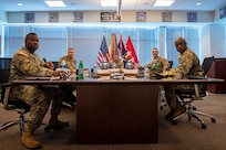 A group of Soldiers sit at a table during a briefing.
