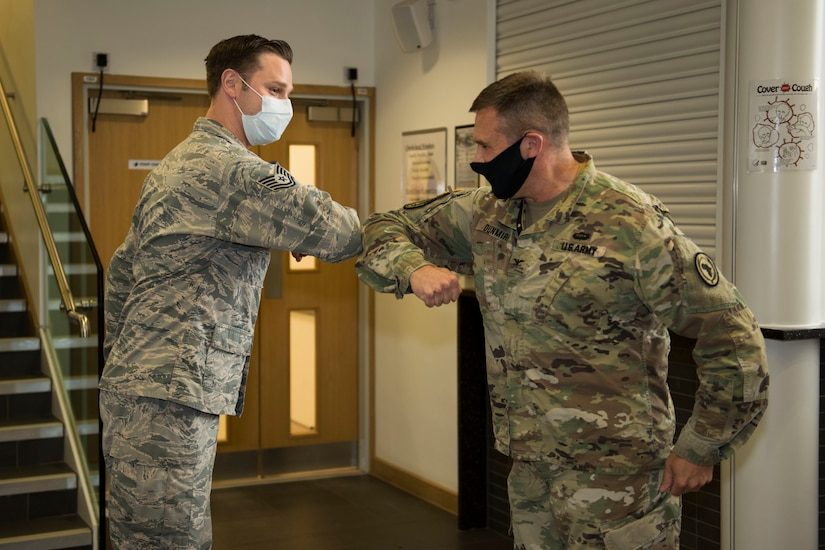 An airman and a soldier, both wearing face masks, exchange an elbow bump during an awards ceremony.