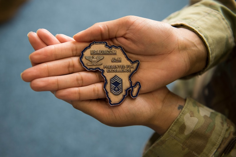 Hands hold a large recognition coin in the shape of the African continent and inscribed for excellence on behalf of U.S. Africa Command.