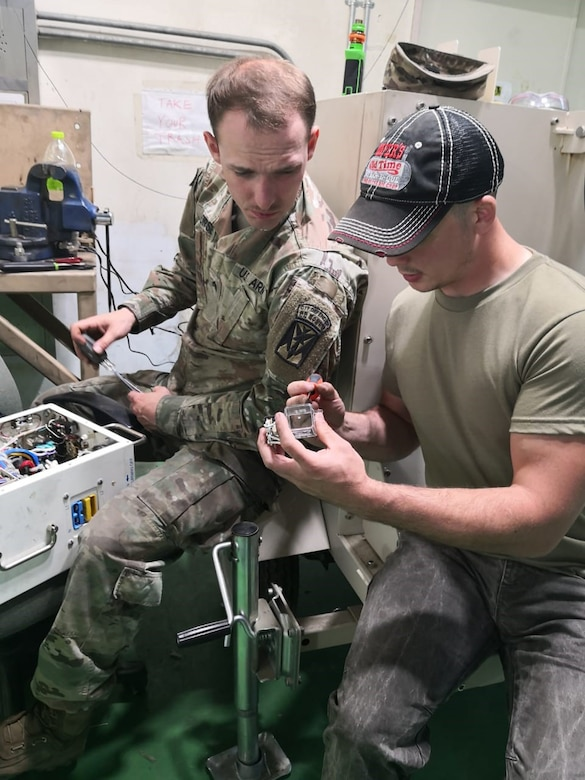 Phot of generator Technician Johnathan Persinger, right, works with Soldiers to repair environmental control units and generators