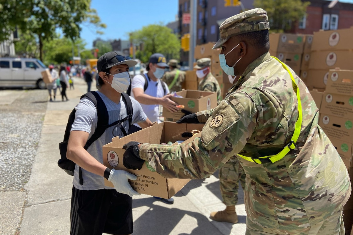 A soldier wearing a mask hands a box of food to a civilian in a mask.