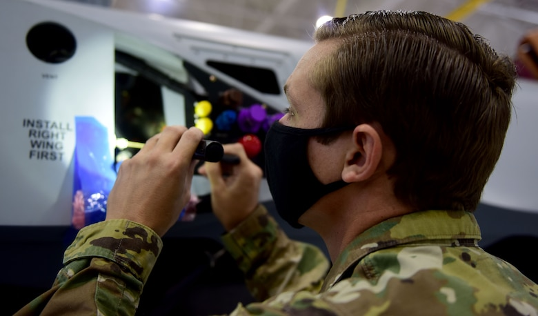 Staff Sgt. Anthony, 432nd Aircraft Maintenance Squadron crew chief, checks inside the panels of an MQ-9 Reaper.