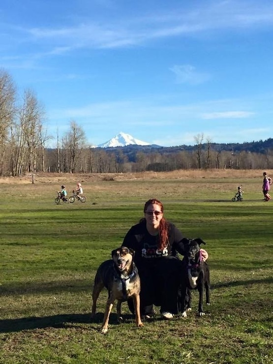 A woman poses in a grassy field with two large dogs. A snowy mountain is in the background.