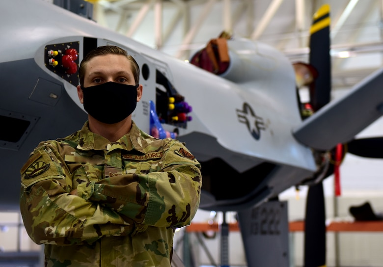 Staff Sgt. Anthony, 432nd Aircraft Maintenance Squadron crew chief, stands in front of an MQ-9 Reaper at Creech Air Force Base, Nev.