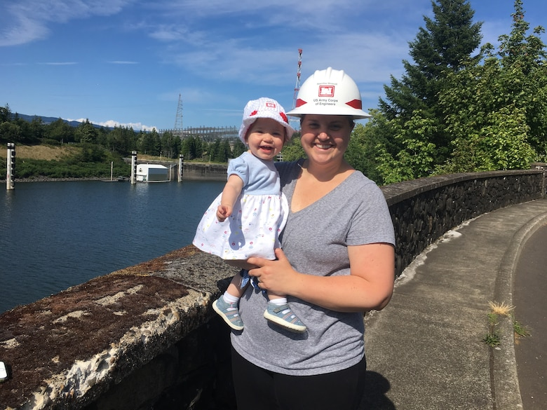 A woman in a hard hat holds a baby in a bonnet near Bonneville Dam.