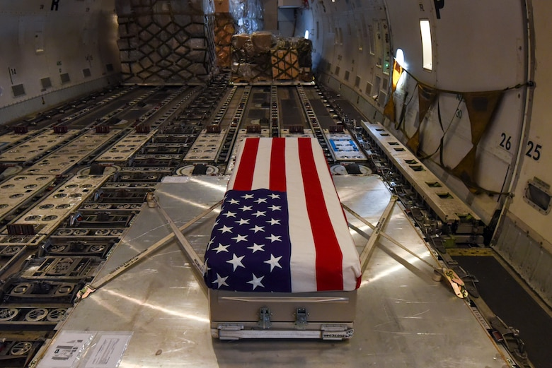 An American Flag is draped over a transfer case on aircraft