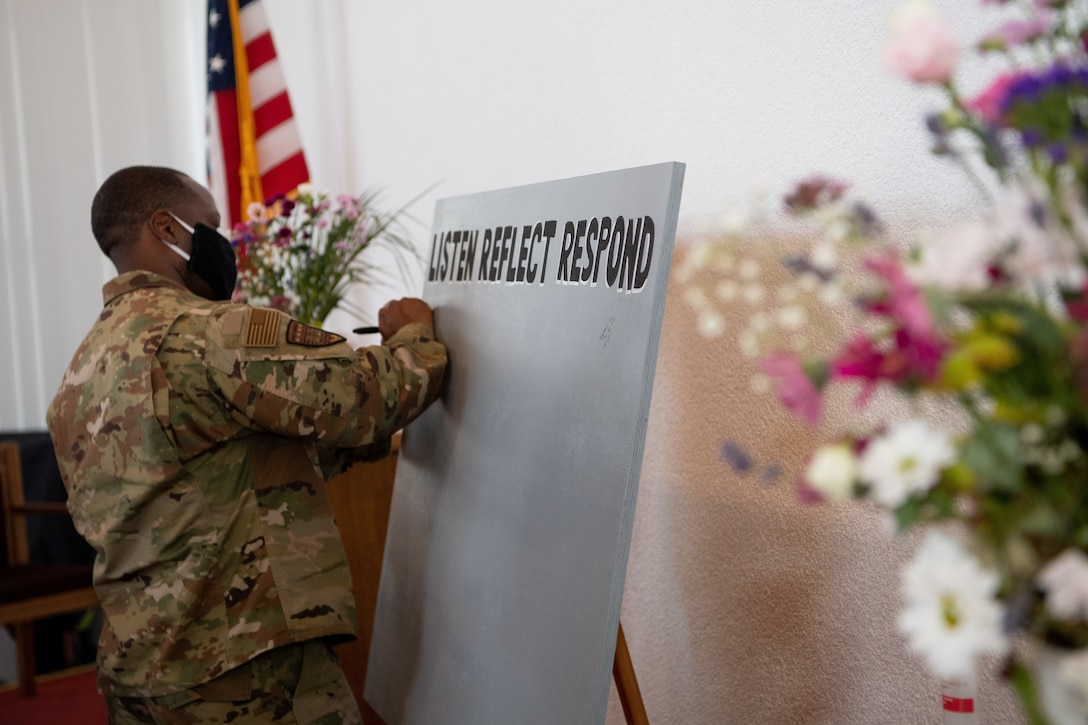 U.S. Air Force Brig. Gen. Ronald E. Jolly Sr., U.S. Air Forces in Europe and Air Forces Africa logistics, engineering and force protection director, signs a message board during the Juneteenth: Vigil for Healing event at Ramstein Air Base, Germany, June 19, 2020.