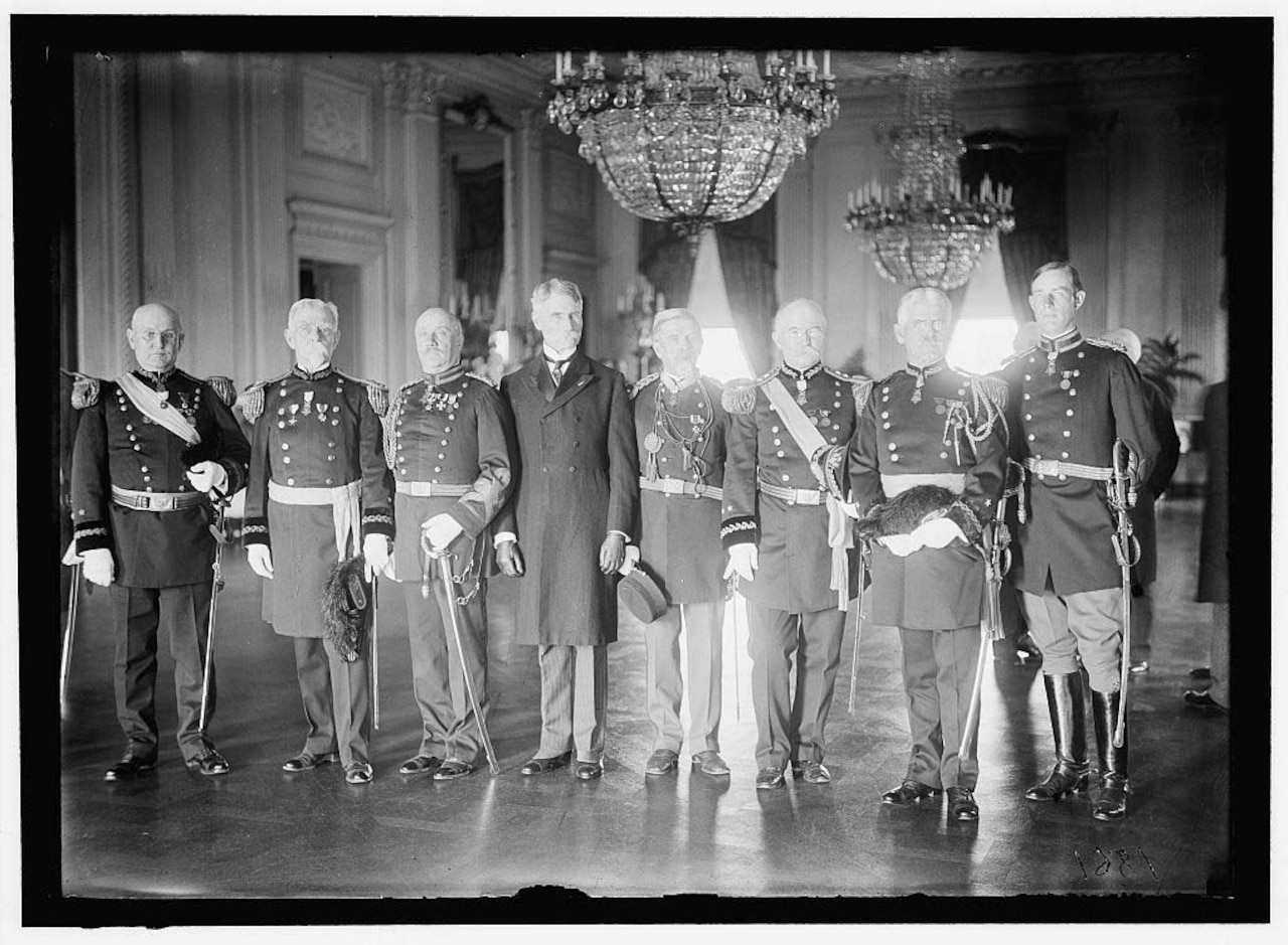 Eight men, seven of whom wear Army dress uniforms, stand in a line in a reception room at the White House.