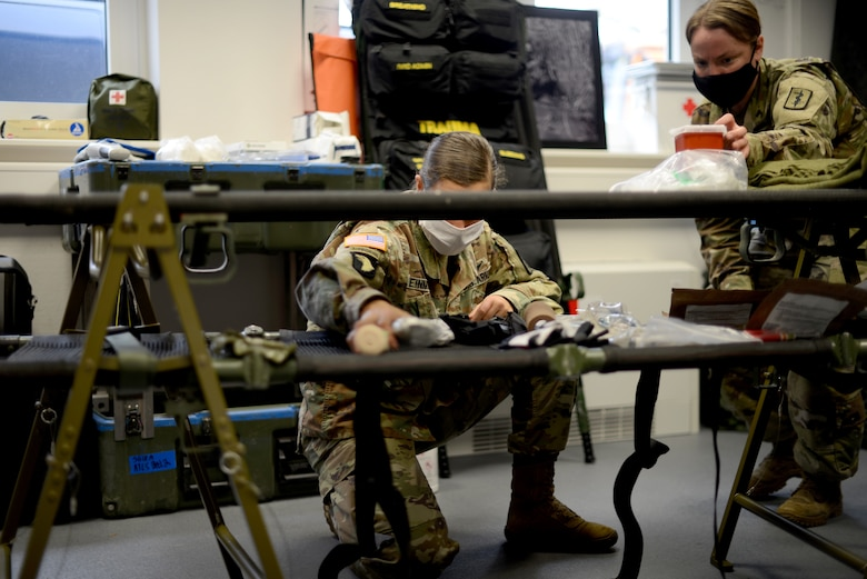 U.S. Army Capt. Jessica Weinman, 67th Forward Resuscitative Surgical Team emergency nurse, center, and Sgt. Sara Lind, 67th FRST combat medic, right, set up the resuscitation section for patient care prior to a training scenario at the Medical Simulation Training Center, Ramstein Air Base, June 18, 2020.