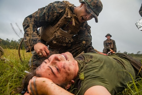 A U.S. Navy Petty Officer 3rd Class Christian Hart, a hospital corpsman with 2d Battalion, 2d Marine Regiment, 2d Marine Division (MARDIV), primes an intravenous fluid bag during a 10-mile trauma run at Camp Lejeune, North Carolina, June 17, 2020. The sailors participated in the HM3 (FMF) Aaron A. Kent Challenge, a three-day event consisting of physical fitness analyses, basic corpsman history, and practical knowledge of trauma treatment in a simulated combat environment. The event was held to honor corpsman who lost their lives in the heat of battle. (U.S. Marine Corps photo by Lance Cpl. Patrick King)