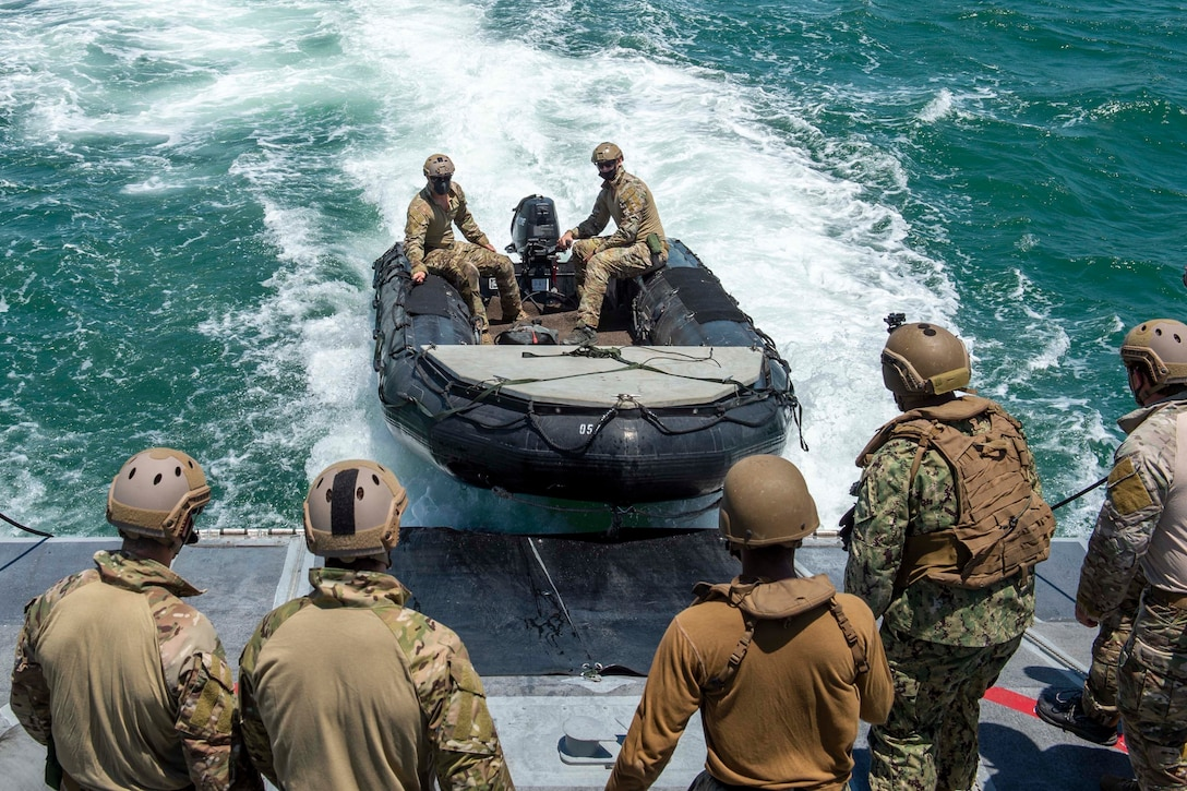 A group of sailors watch as a rubber raiding craft is launched into the water.