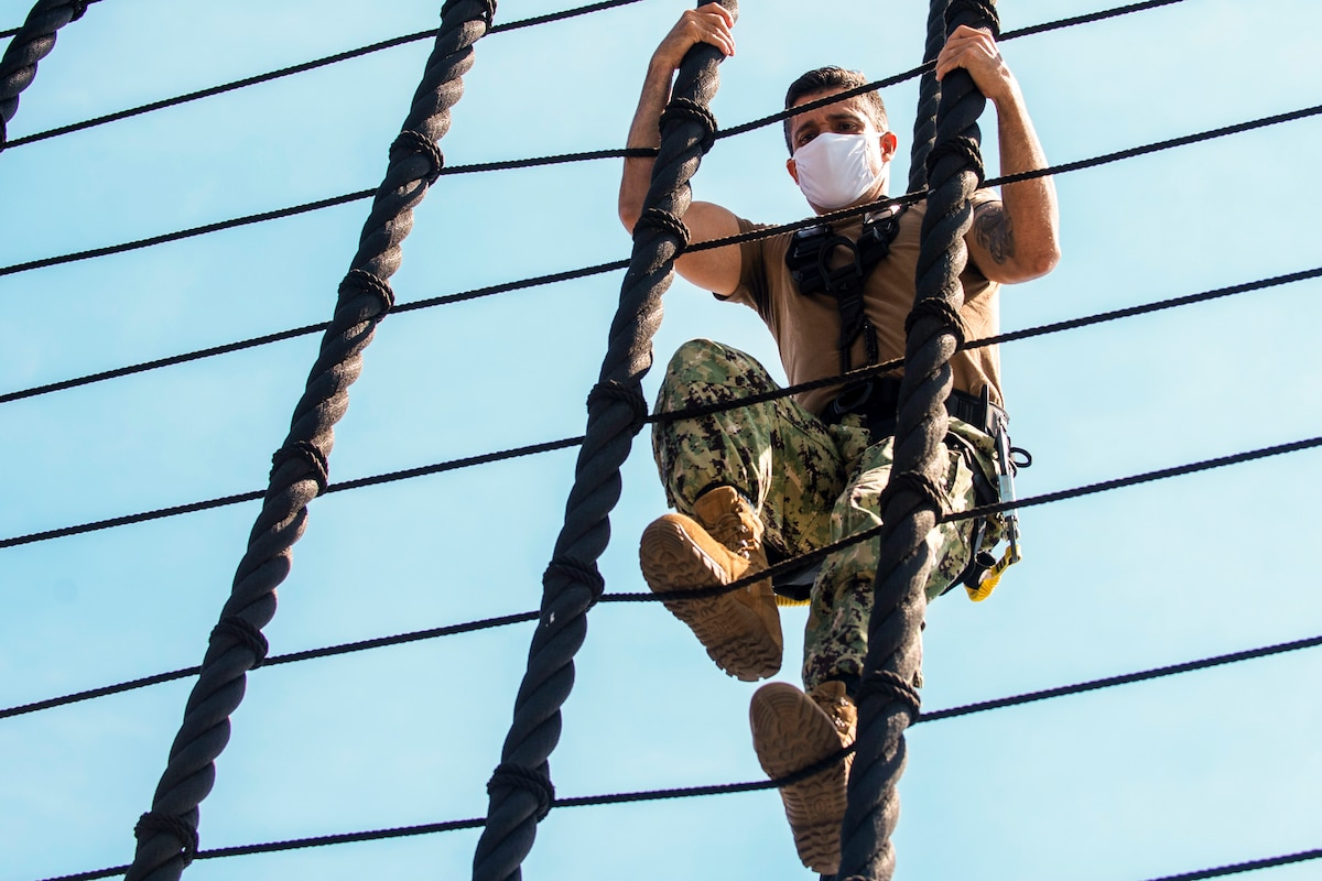 A sailor in protective gear climbs ropes.