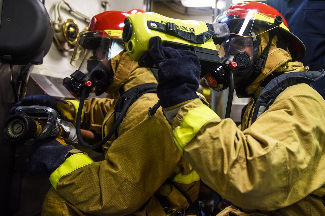 Two sailors use thermal imaging equipment during training.