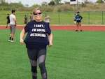 U.S. Army Reserve Master Sgt. Susan Benavidez, an operations non-commissioned officer with the 211th Regional Support Group and Hood Mobilization Brigade, shows off her social distancing shirt during a workout session on March 25, 2020 at Fort Hood stadium. Soldiers with the Hood Mob Brigade practiced social distancing during their fitness sessions.     U.S. Army photo by Staff Sgt. Jasmine Edden