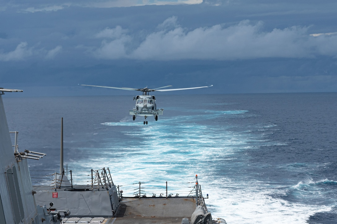 A helicopter prepares to land on a ship.