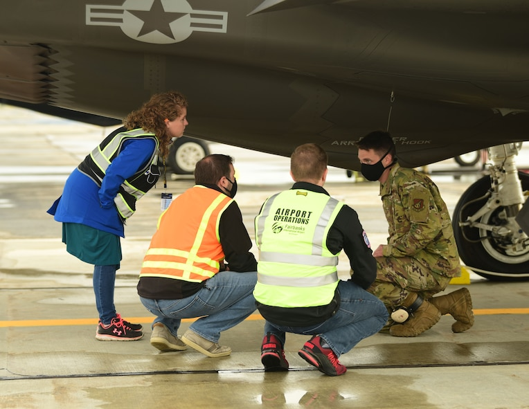 U.S. Air Force Tech. Sgt. Theodore Crowley, a 356th Aircraft Maintenance Unit F-35A Lightning II crew chief, explains some basic features and functions of the F-35A to representatives from Omni Logistics Inc. at the Fairbanks International Airport, June 24, 2020.