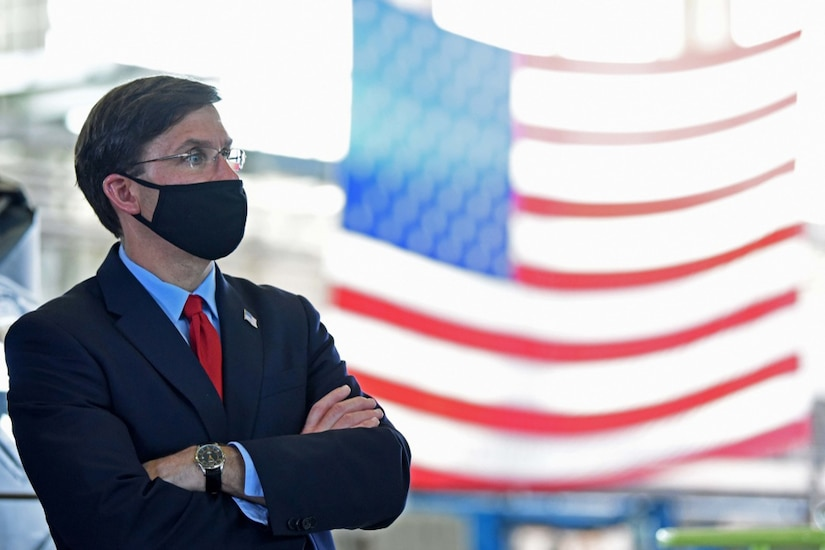A man dressed in a business suit and wearing a face mask stands with his arms folded and looks into the distance.