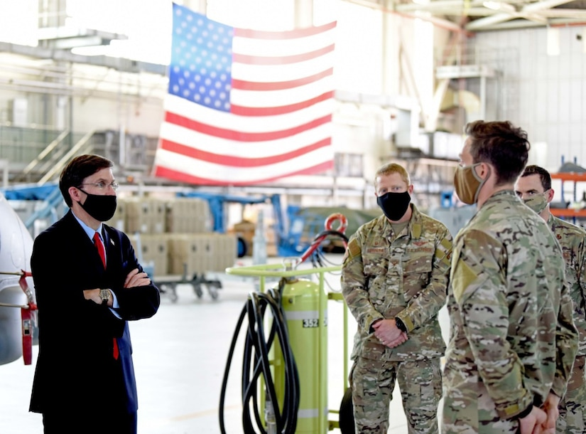 A man dressed in civilian clothing stands facing three men wearing military uniforms in a hangar with a U.S. flag hanging from the ceiling. All are wearing face masks.