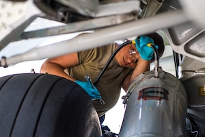 Hydraulics technician attaches a hose to the landing gear of a C-17 Globemaster III