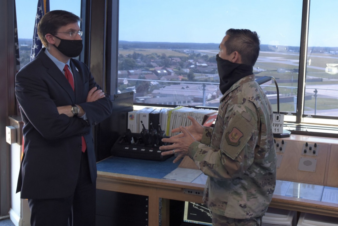 Two men wearing face masks, one dressed in a business suit and one dressed in a military uniform, talk in a small office next to a window overlooking the countryside.
