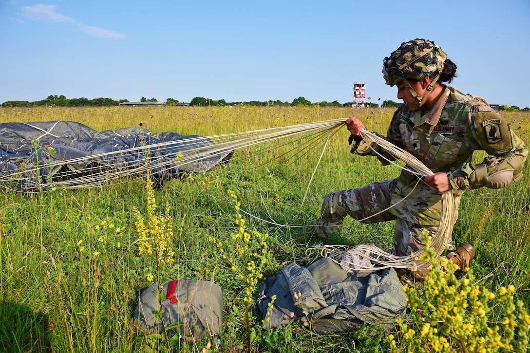 A paratrooper on the ground gathers up a parachute  after a jump.