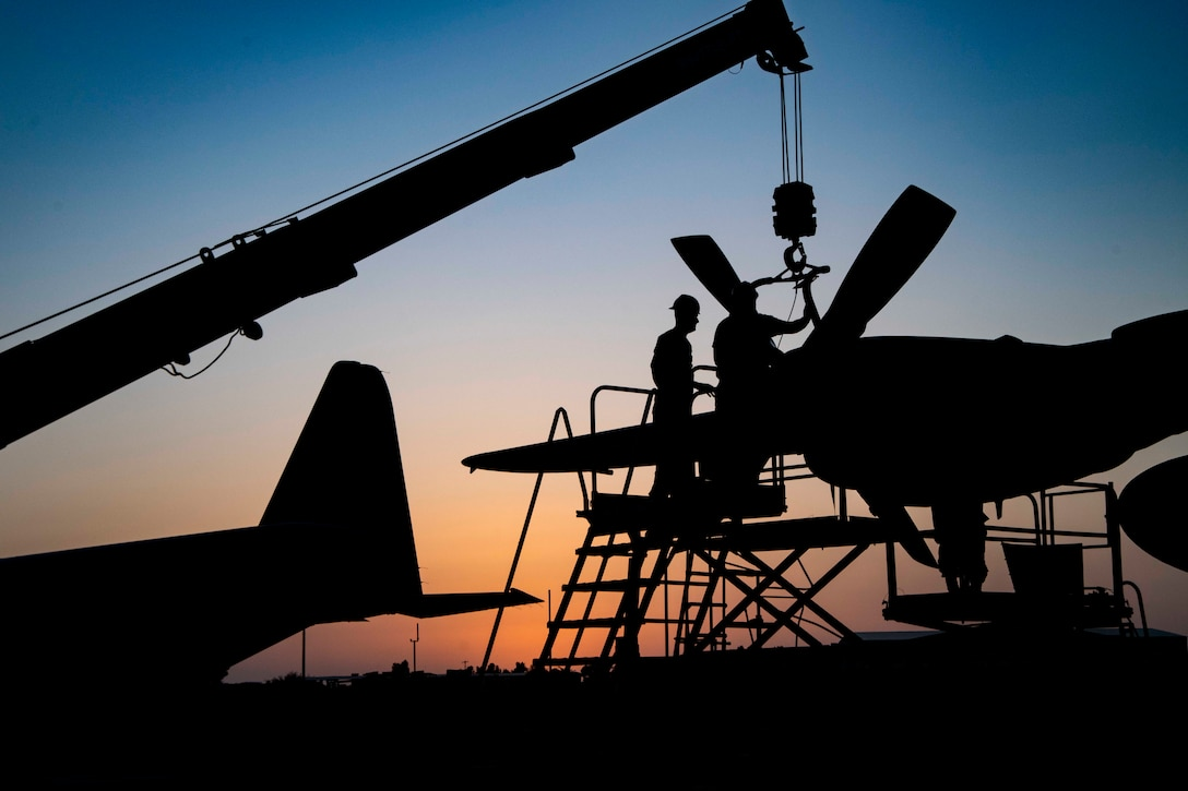 Two airmen work on an aircraft in silhoutte.