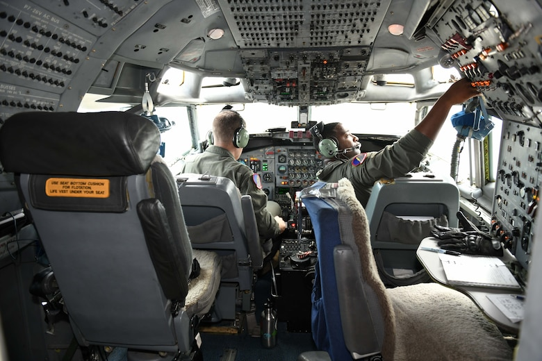 Photo shows two Airmen in the cockpit of an aircraft.