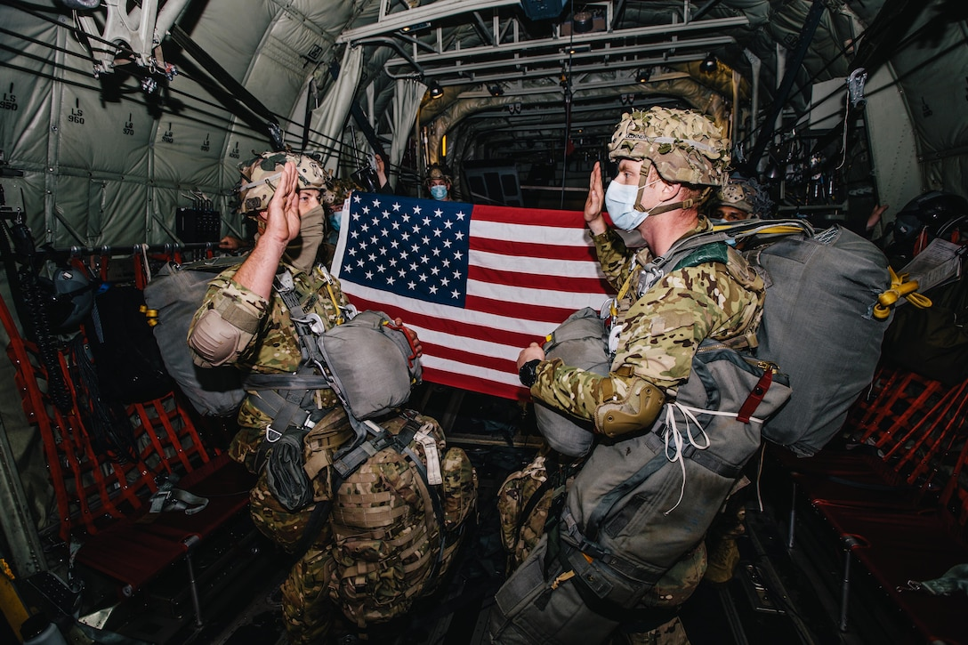 A soldier reenlists another aboard an aircraft.