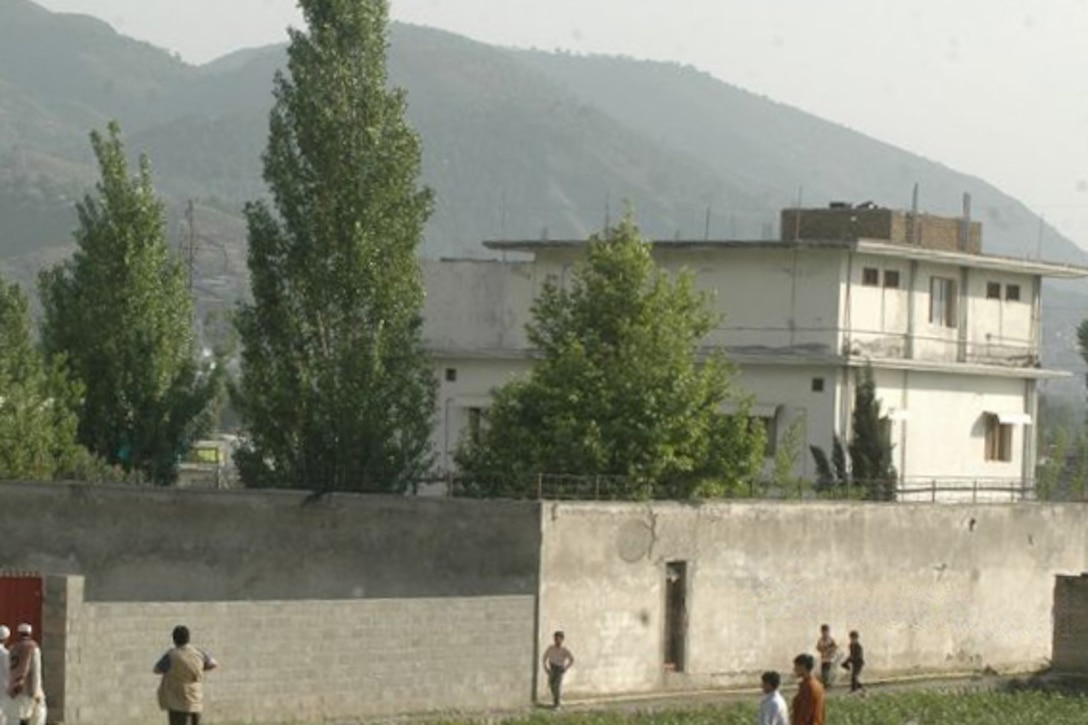 People approach a wall surrounding a compound.