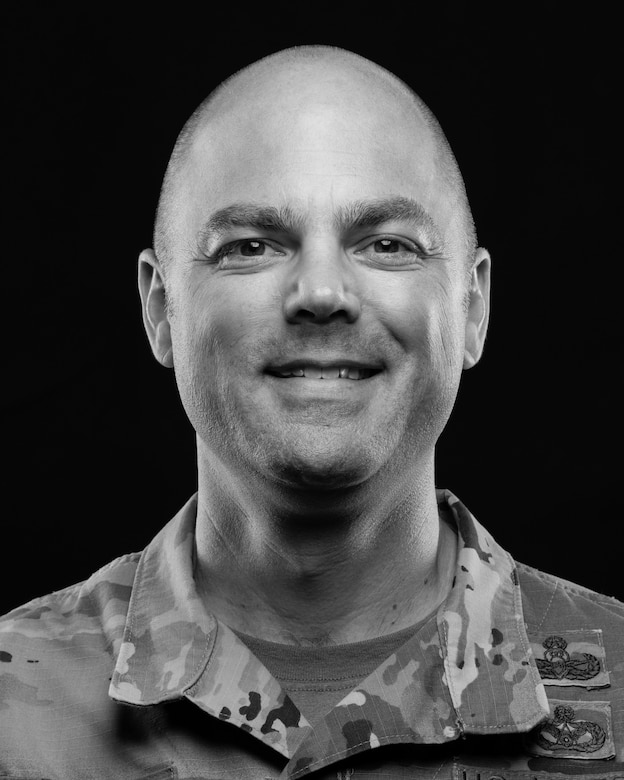 Chief Master Sgt. Jeremiah Grisham, 436th Mission Support Group superintendent, poses for a photo June 16, 2020, at Dover Air Force Base, Delaware. Grisham was one of a handful of Team Dover members photographed for a base diversity project. (U.S. Air Force photo by Mauricio Campino) (This image was created in color and changed to black and white.)