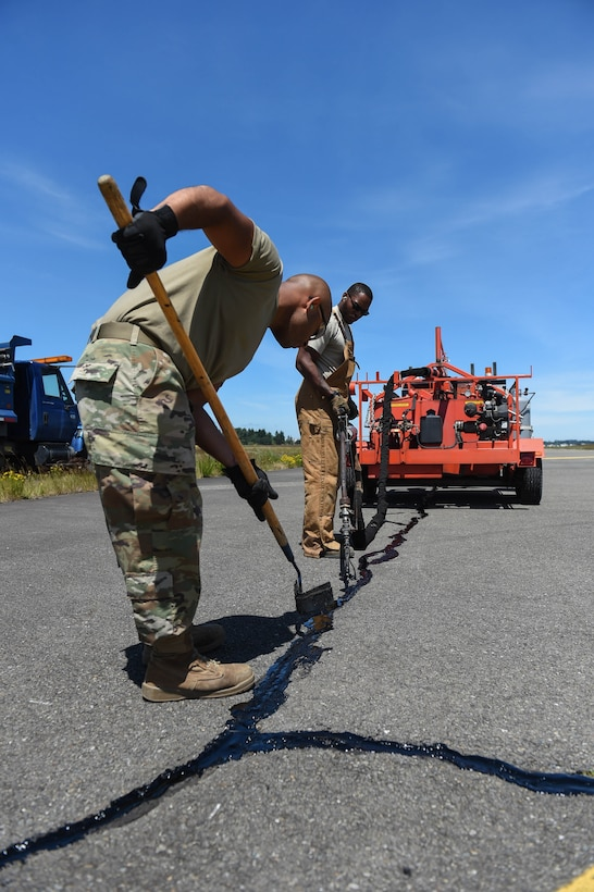 Airman 1st Class Felipe Reyes-Cedeno, left, and Senior Airman Irvin Matthews, right, 627th Civil Engineer Squadron pavements and construction equipment technicians work together to reseal a crack in the McChord Field flight line on Joint Base Lewis-McChord, Wash., June 25, 2020. In a three-person resealing team, one person drives the truck moving the tar kettle around, while another operates the tar dispensing handle, and the last person follows them with a squeegee making sure the tar is level with the asphalt. (U.S. Air Force photo by Airman 1st Class Mikayla Heineck)