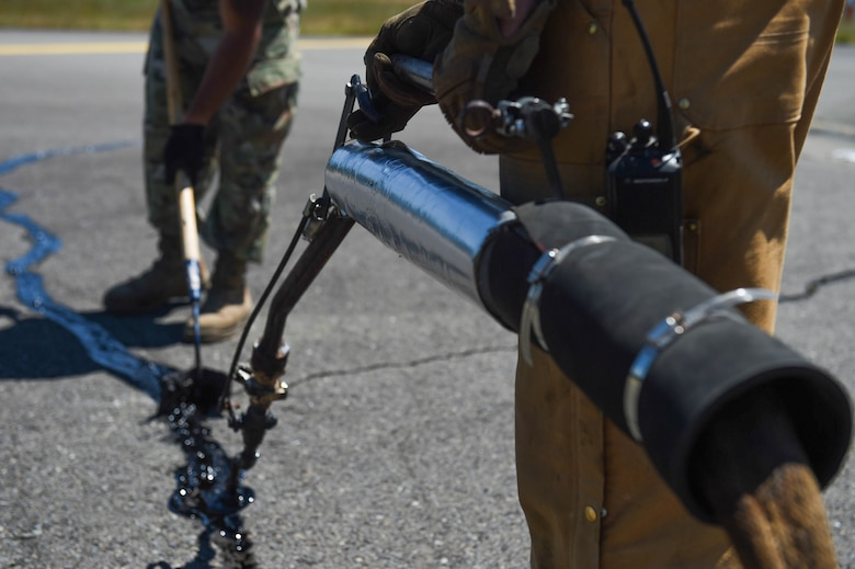 Airman 1st Class Felipe Reyes-Cedeno, left, 627th Civil Engineer Squadron pavements and construction equipment technician, uses a squeegee to level melted tar with the asphalt as Senior Airman Irvin Matthews, right, 627th CES pavements and construction equipment technician, dispenses the tar into the cracks on the McChord Field flight line on Joint Base Lewis-McChord, Wash., June 25, 2020. Filling pavement cracks helps prolong its life by preventing rain and moisture from flowing through the asphalt and eroding it. (U.S. Air Force photo by Airman 1st Class Mikayla Heineck)