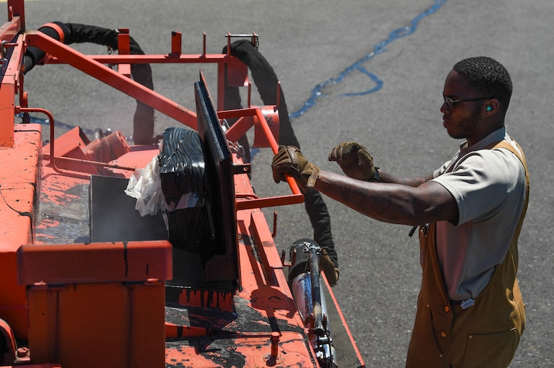 Senior Airman Irvin Matthews, 627th Civil Engineer Squadron pavements and construction equipment technician, dumps a bag of solid tar into a tar kettle to prepare it for use after completing resealing for the day on the McChord Field flight line on Joint Base Lewis-McChord, Wash., June 25, 2020. The tar kettle heats up to about 475 degrees farenheit to keep the tar in a liquid state and ready to dispense. (U.S. Air Force photo by Airman 1st Class Mikayla Heineck)