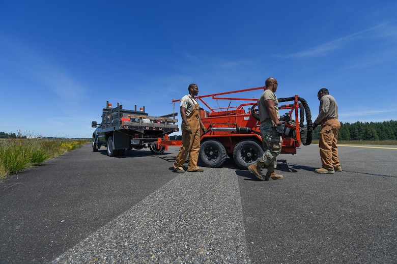 Senior Airman Irvin Matthews, left, Airman 1st Class Felipe Reyes-Cedeno, middle, and Staff Sgt. Adrian Carter, right, 627th Civil Engineer Squadron pavements and construction equipment technicians, secure a tar kettle and dispensing hose to drive back after finishing the resealing of several cracks in the asphalt of the McChord Field flight line on Joint Base Lewis-McChord, Wash., June 25, 2020. Resealing the cracks in the flight line prolongs its life by preventing erosion and is a faster method than replacing entire sections of asphalt. (U.S. Air Force photo by Airman 1st Class Mikayla Heineck)