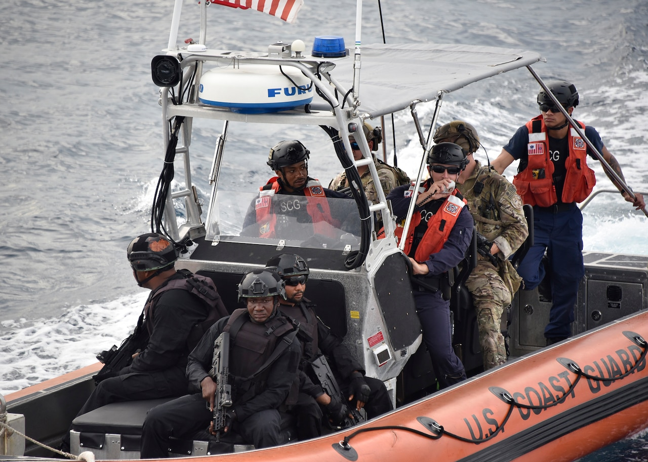 A small boat approaches a Coast Guard cutter.