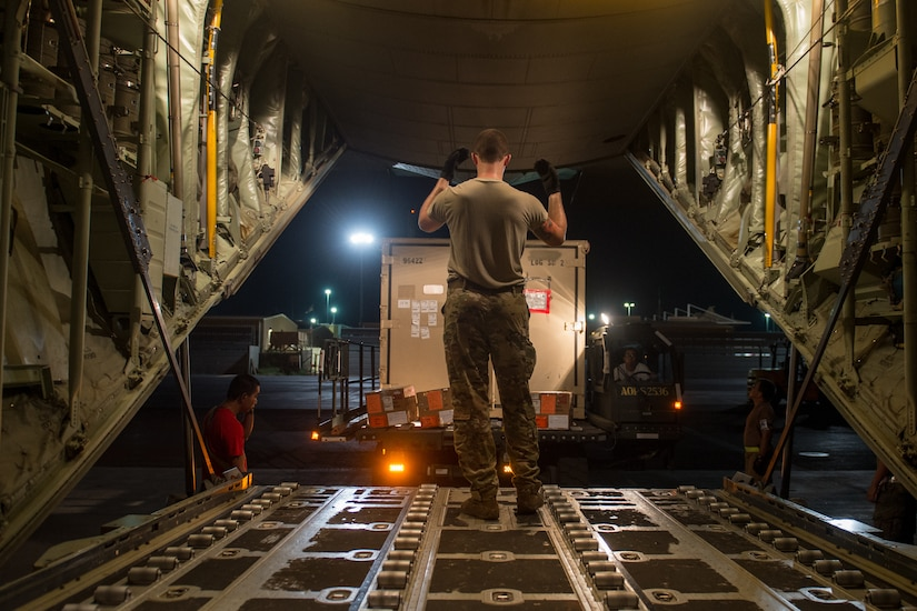 A person in uniform guides a truck as it backs up to the cargo loading area of an airplane.
