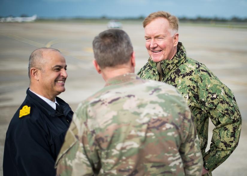 Three men in uniform meet on a flightline.