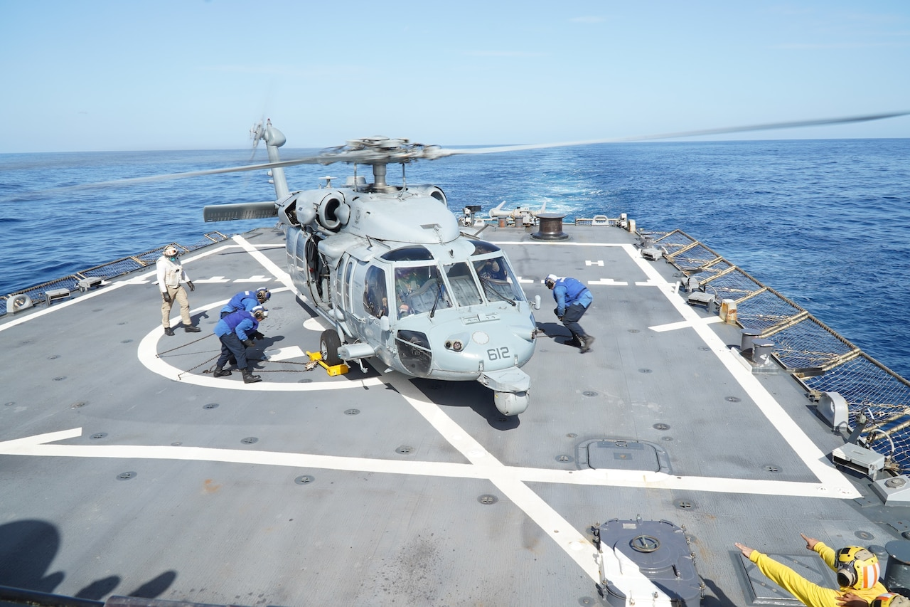 A helicopter has just landed on the deck of a ship.