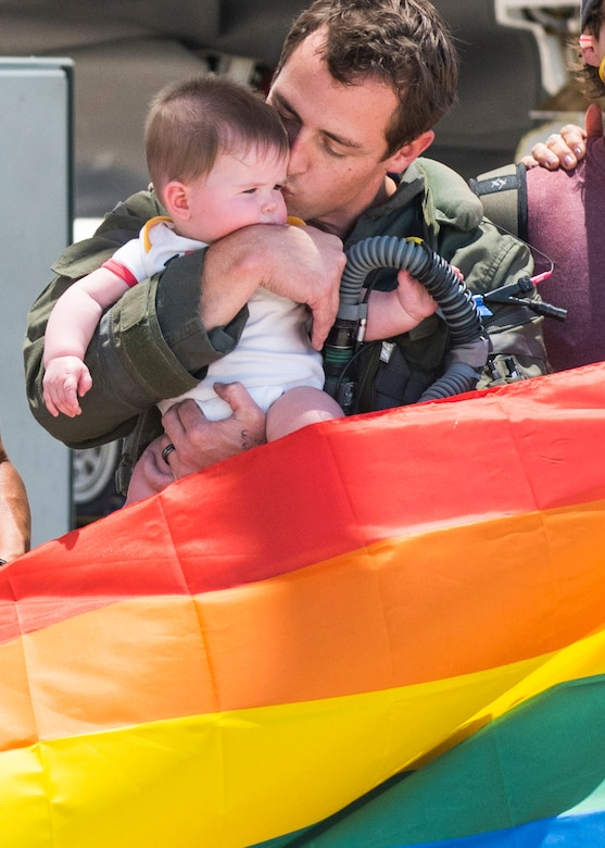 Maj. Tyler McBride, 62nd Fighter Squadron F-35A Lightning II instructor pilot, embraces his daughter after a Pride Month flyby June 26, 2020, at Luke Air Force Base, Ariz.