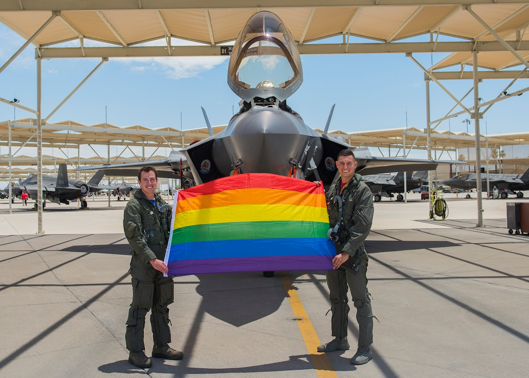 Maj. Tyler McBride, 62nd Fighter Squadron F-35A Lightning II instructor pilot, and Capt. Justin Lennon, 56th Training Squadron F-35 instructor pilot, hold an LGBTQ+ Pride flag after a Pride Month flyby June 26, 2020, at Luke Air Force Base, Ariz.