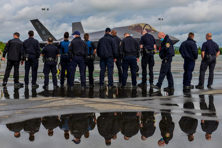 Fairbanks International Airport (FAI) Police and Fire Department personnel observe a U.S. Air Force F-35A Lightning II assigned to the 356th Fighter Squadron on the airport runway in Fairbanks, Alaska, June 24, 2020.