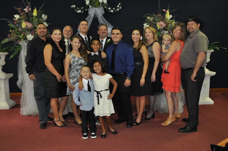 Marvin Tucker, emergency manager, 452nd Air Mobility Wing, and his new husband, Joshua Delgado, (back row, center) pose in the base chapel with Tucker's family after the couple exchanged vows and became the first same-sex couple to be married at the historic March Air Reserve Base on Aug. 3, 2013.